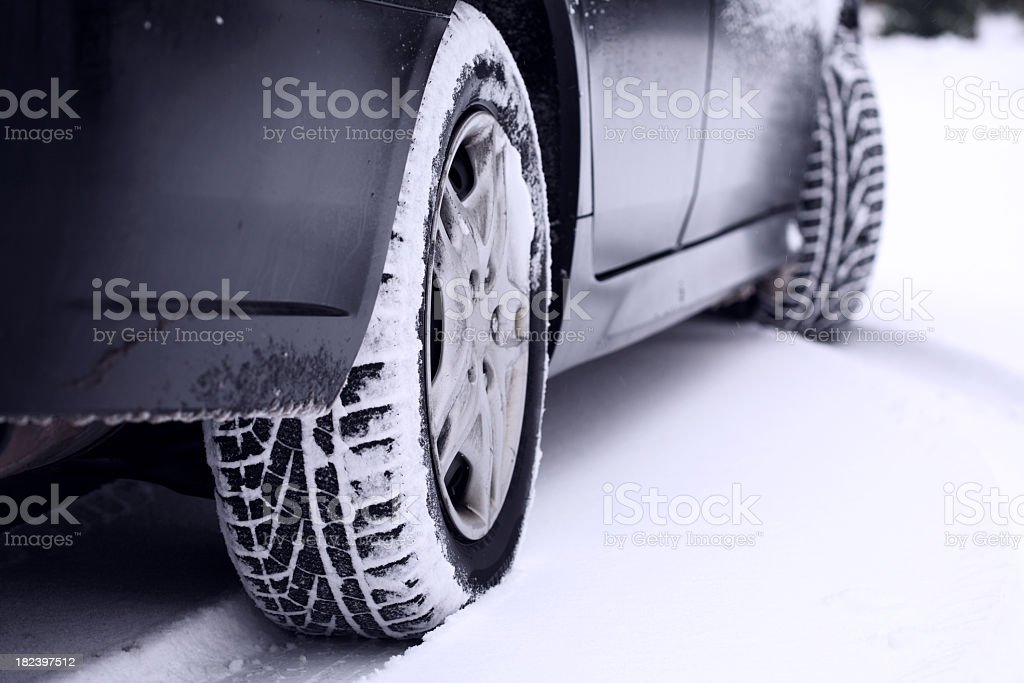 Car tires leaving a track in the snow stock photo