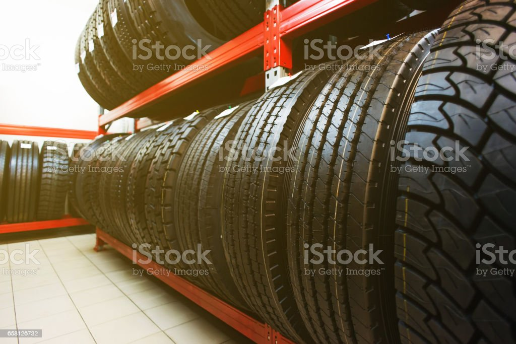Car tires on warehouse. Many black tires stock photo