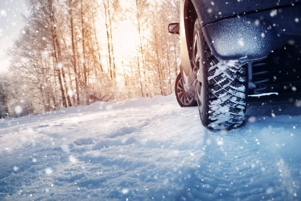 car tires on winter road covered with snow - car chill foto e immagini stock