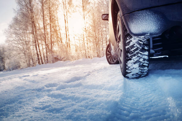 Car tires on winter road covered with snow stock photo