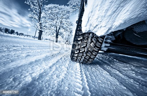 istock Car tires on winter road 469697297