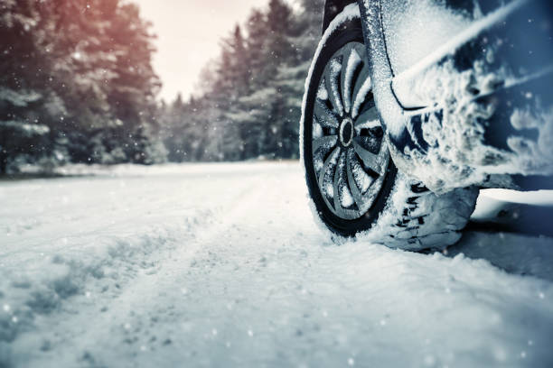 Car tires on winter road stock photo