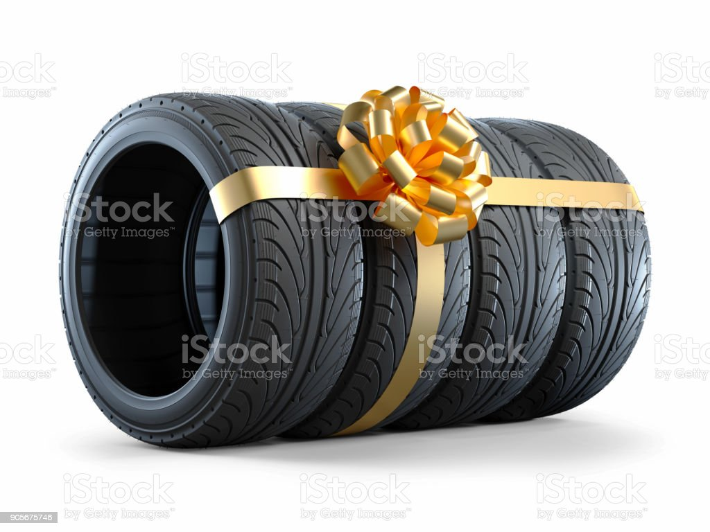 Car tires wrapped in a gift ribbon with a bow stock photo