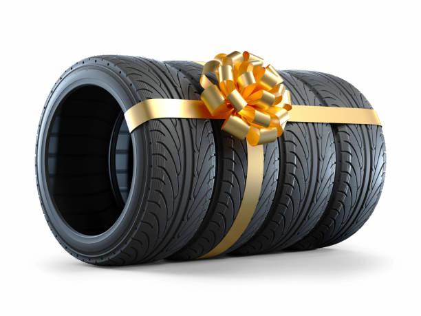 pkw-reifen in einem geschenkband mit schleife verpackt - autoschleifen stock-fotos und bilder