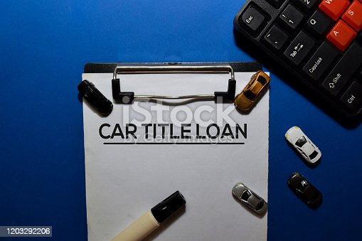 Car Title Loan write on document with toys car isolated blue background.