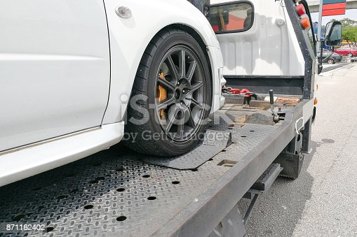 istock Car towed onto flatbed tow truck with hook and chain 871162402