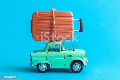 Suitcase on car roof on blue background minimal creative travel concept.