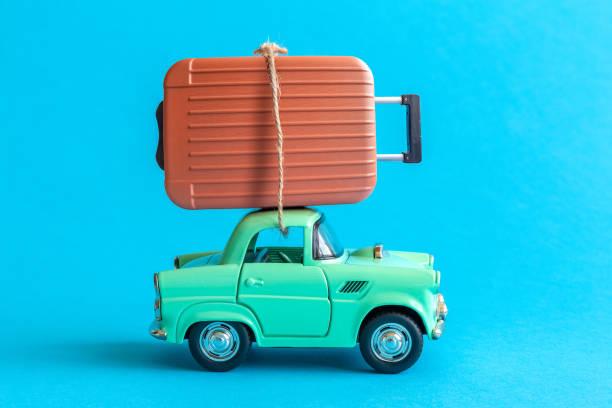 Juguete de coche y equipaje abstracto aislado en azul. - foto de stock