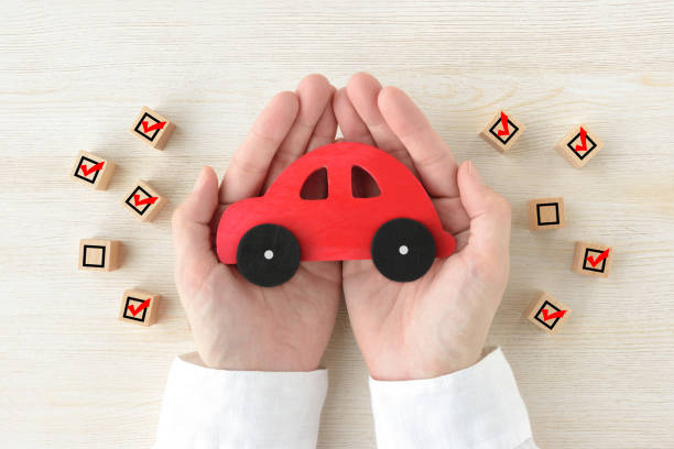 Car toy covered by human's hands surrounded by wooden blocks with checking marks stock photo
