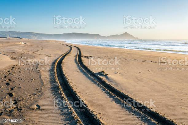Photo of A 4WD car track in a wild beach sand going towards an endless infinite horizon at the Chilean coastline in Puertecillo beach, an amazing place for visiting and having a wonderful day, Chile
