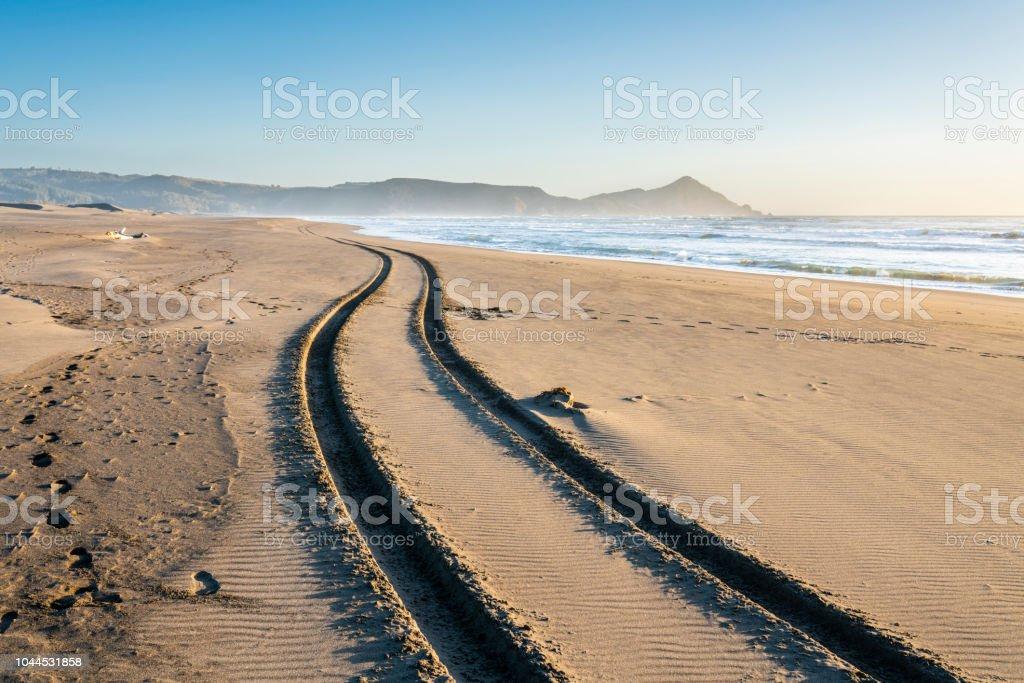 A 4WD car track in a wild beach sand going towards an endless infinite horizon at the Chilean coastline in Topocalma beach, Puertecillo, Chile stock photo