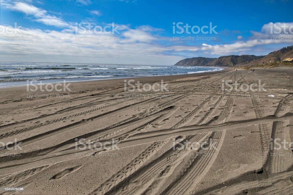 A 4WD car track in a wild beach sand going towards an endless infinite horizon on an amazing landscape at the Chilean coastline in Puertecillo beach, Chile stock photo
