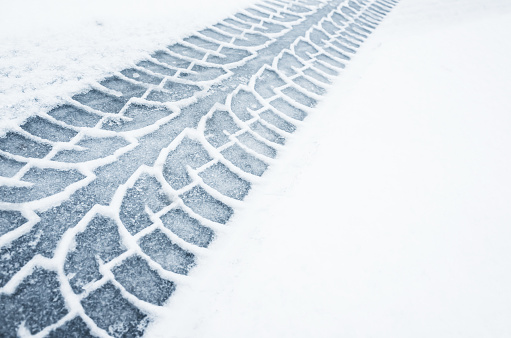 Car track on a wet snowy road, closeup