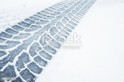 istock Car track on a wet snowy road, closeup 885541870