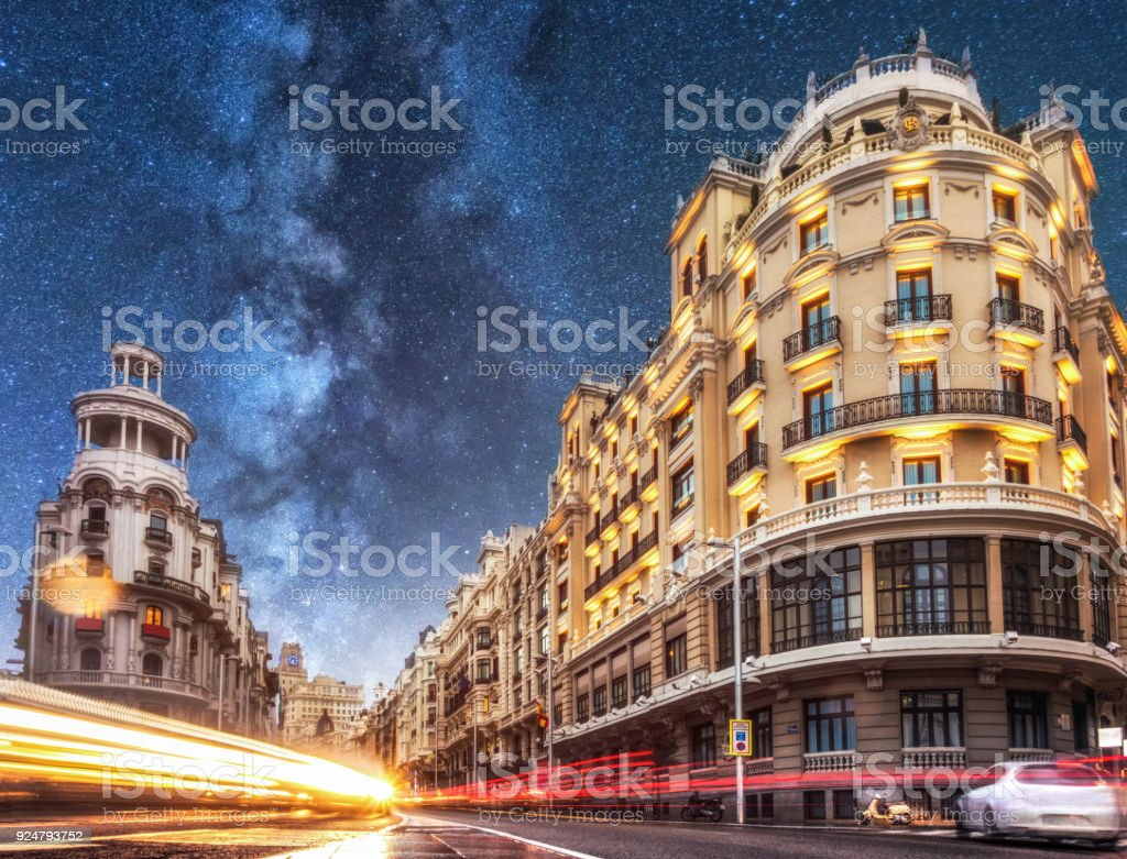 car trails in gran via at night with milky way. madrid. spain stock photo