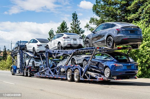 Jun 6, 2020 / CA / USA - Car transporter carries new Tesla Model Y (on the upper level) and Tesla Model 3 (on the lower level) vehicles on a freeway in San Francisco Bay Area