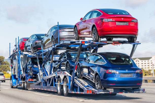 Car transporter carrying Tesla Model 3 new vehicles Aug 10, 2019 Burlingame / CA / USA - Car transporter carries Tesla Model 3 new vehicles on a freeway in San Francisco bay area, back view of the trailer; tesla motors stock pictures, royalty-free photos & images