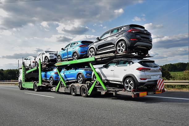 car transporter driving on the highway - autotransporter stock-fotos und bilder