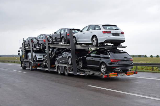 autotransporter mit audi und bmw fahrzeuge fahren auf der autobahn - autotransporter stock-fotos und bilder