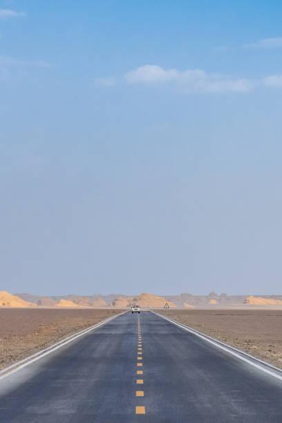 Car traveling on road in gobi desert in Dunhuang Yardang National Geopark, Gansu, China stock photo