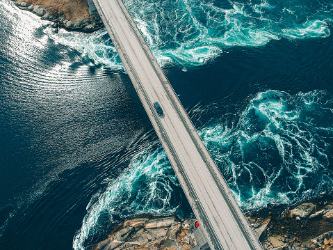 Torrents creating patterns in turquoise water underneath a bridge with a car traveling across it at Salstraumen near Bodo Norway