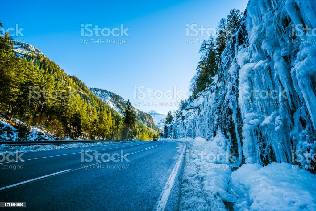 Car Trip - many icicles along road in mountains on winter day stock photo