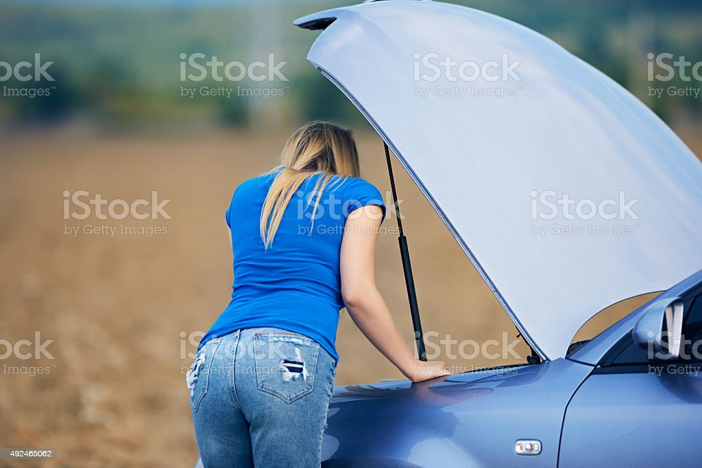 rear view of worried woman looking at her car engine and having...