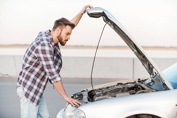 Car trouble. Serious young man holding hands on vehicle hood and looking inside it while standing outdoors vehicle hood stock pictures, royalty-free photos & images