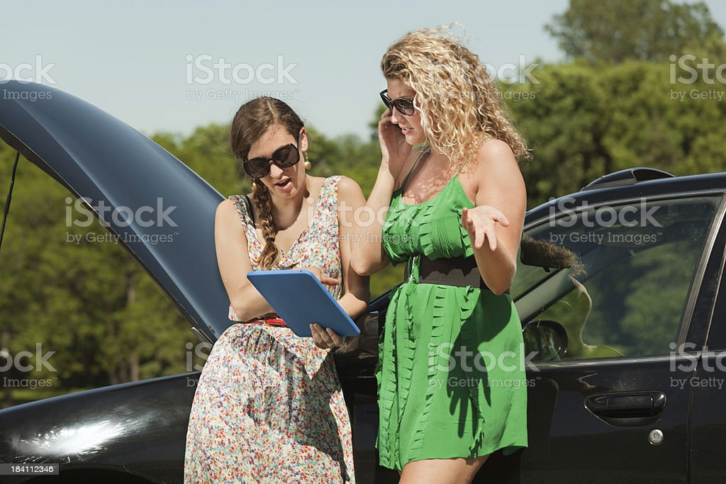 Car Trouble Travelers Using Tablet Computer, Mobile Phone for Help royalty-free stock photo