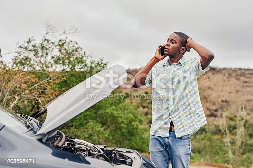 Cropped shot of a handsome young man calling roadside assistance while standing next to his broken down car outdoors