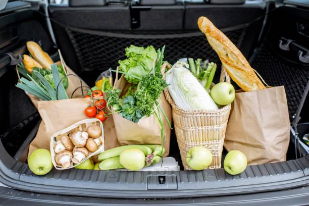 Auto koffer met boodschappentassen en producten foto