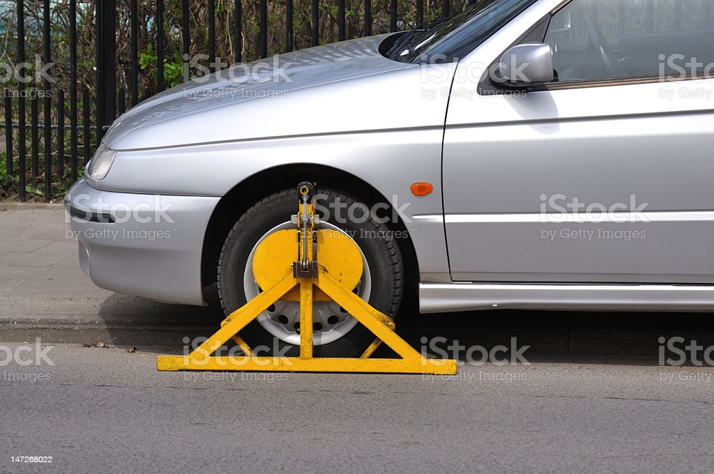 A car unable to move because a wheel clamp is on its tire stock photo