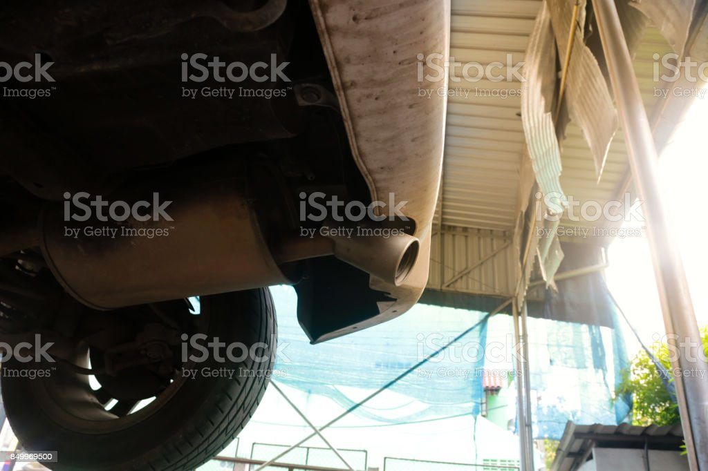 Car undercarriage and exhaust pipe in the garage shop. stock photo