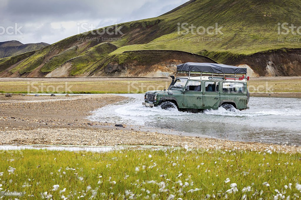 4WD car wades river in Landmannalaugar, Iceland stock photo