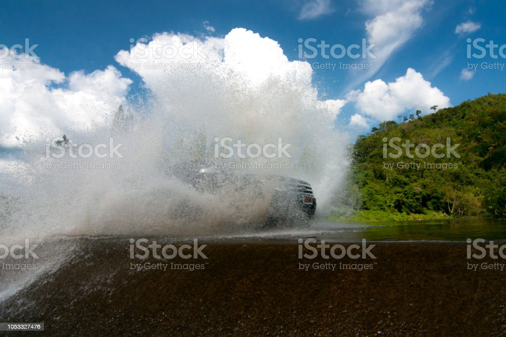 4WD car wades river in suanphueng stock photo
