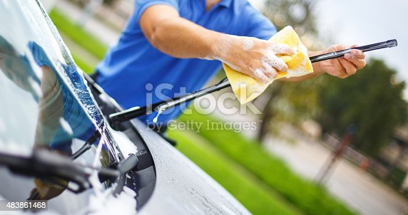 Closeup of unrecognziable adult man washing his car at a parking lot. He's using yellow spong and soap and cleaning windshield wipers. The man is wearing blue polo shirt.