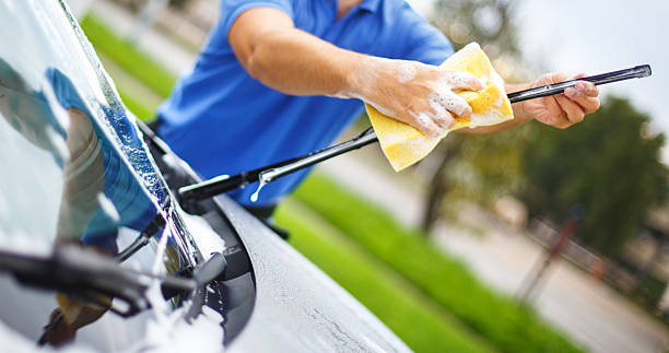 Car wash. Closeup of unrecognziable adult man washing his car at a parking lot. He's using yellow spong and soap and cleaning windshield wipers. The man is wearing blue polo shirt. windshield wiper stock pictures, royalty-free photos & images