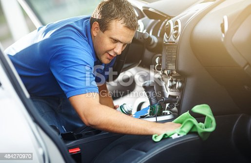 Mid-aged man cleaning the interior of his car at parking lot while sitting in driver's seat. He's using green soft cloth to clean passeneger seat .He has brown hair and wears blue polo shirt.