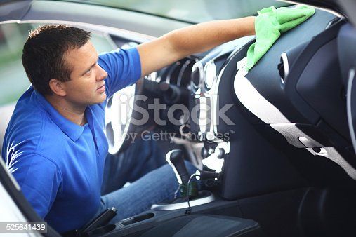 Man cleaning dashboard of his car.