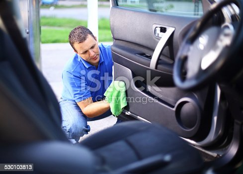 Mid-aged man cleaning the interior of his car at parking lot while sitting in driver's seat. He's using green soft cloth to clean driver's seat and door.He has brown hair and wearing blue polo shirt.