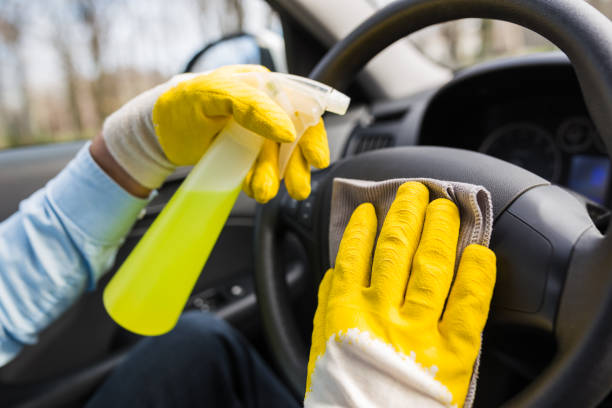 Automóvil lavado trabajador desinfectando el interior del vehículo. - foto de stock
