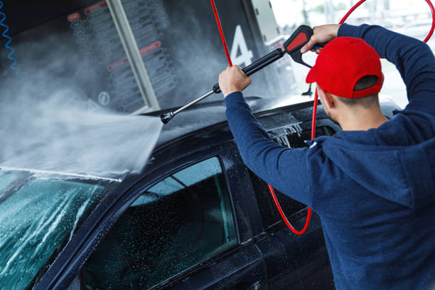 Car wash worker is washing client's car stock photo