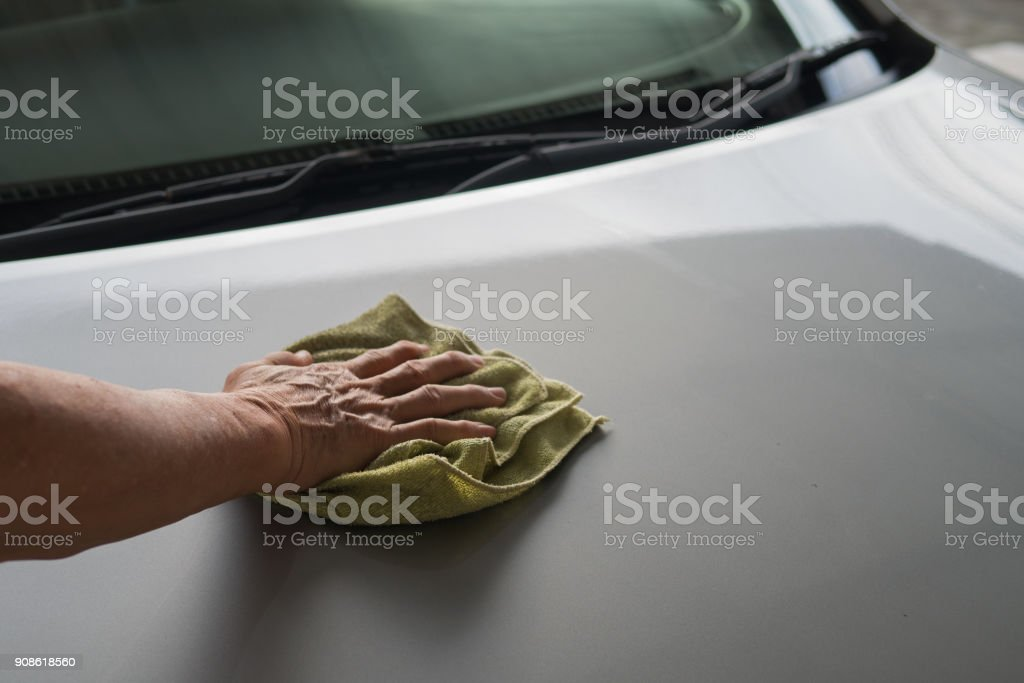Car washing by hand holding microfiber cloth wiped for car care service stock photo