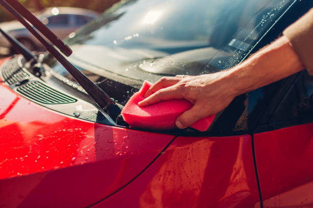 Car washing. Man cleaning car with soapy sponge outdoors. Close-up