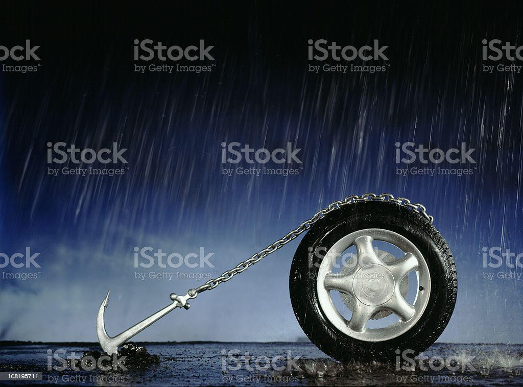 Car Wheel Anchored to Ground in Pouring Rain stock photo