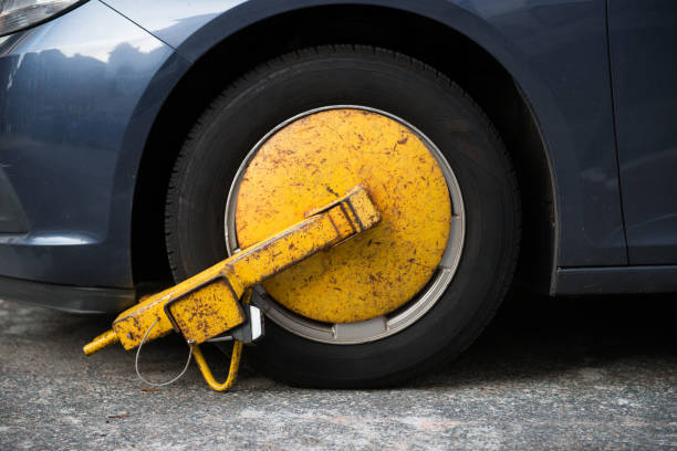 car wheel blocked by wheel lock because illegal parking violation - trapped stock pictures, royalty-free photos & images