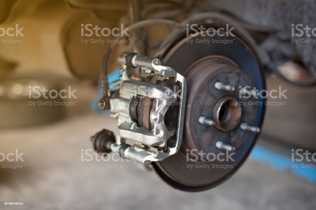car wheel brake disc and shoes of lifted automobile at repair service station stock photo
