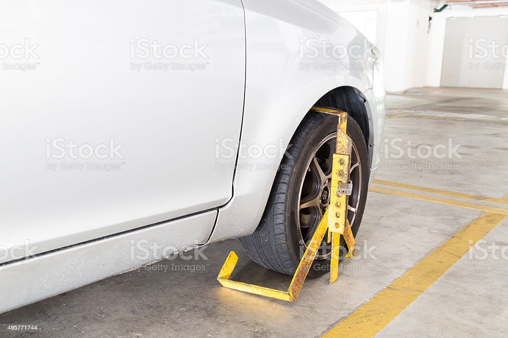 Car wheel clamped for illegal parking violation at car park stock photo