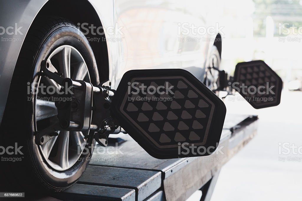 Car wheel fixed with computerized wheel alignment machine clamp stock photo