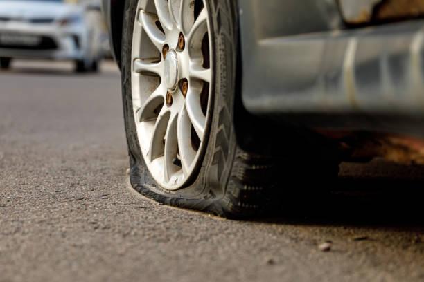 Autorad mit einem platten Reifen auf der Fahrbahn. Bild eines Unfalls, Schaden, Panne zur Illustration zum Thema Reparatur, Versicherung. Selektiver Fokus. – Foto